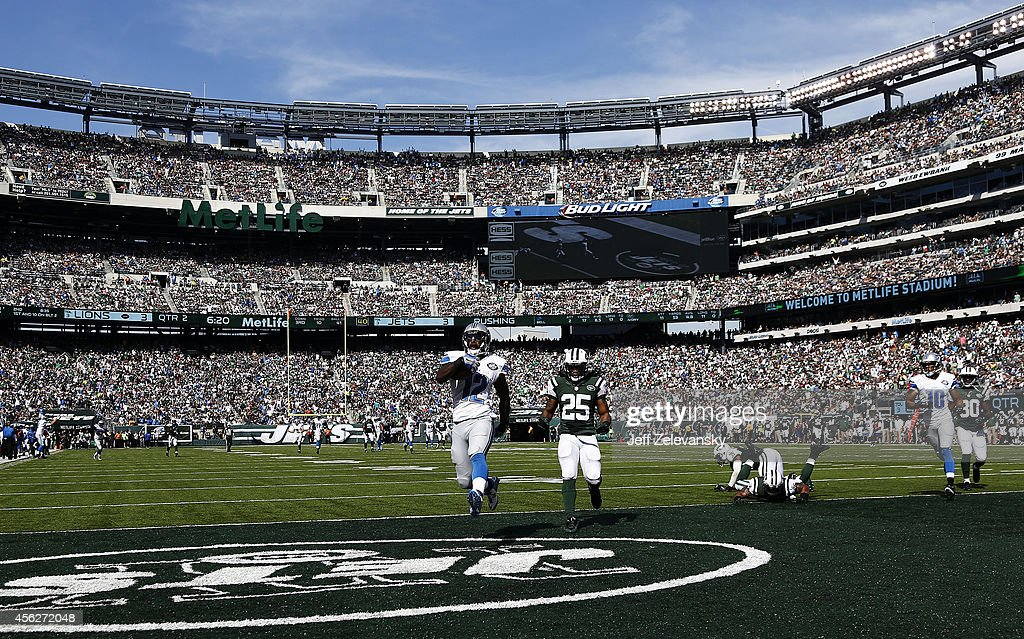 Jeremy Ross of the Detroit Lions scores a 59yard touchdown in the in the second quarter as Calvin Pryor of the New York Jets looks on at MetLife...