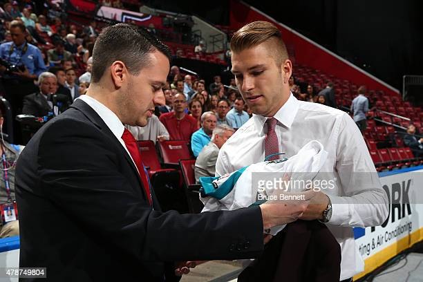Jeremy Roy puts on his jersey after being selected 31st overall by the San Jose Sharks during the 2015 NHL Draft at BBT Center on June 27 2015 in...