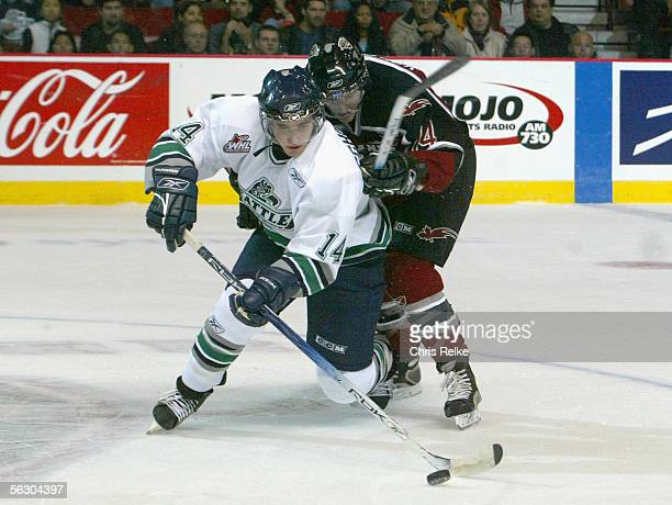 Jeremy Schappert of the Seattle Thunderbirds handles the puck under pressure from the Vancouver Giants during the WHL hockey game on October 2 2005...