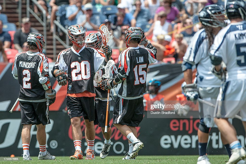 Jeremy Sieverts #20 of the Denver Outlaws celebrates a second half goal with teammates, including <a gi-track='captionPersonalityLinkClicked' href=/galleries/search?phrase=Brendan+Mundorf&family=editorial&specificpeople=5984390 ng-click='$event.stopPropagation()'>Brendan Mundorf</a> #2 and Eric Law #15 during a Major League Lacrosse game at Sports Authority Field at Mile High on July 27, 2013 in Denver, Colorado. The Outlaws beat the Bayhawks 14-12.
