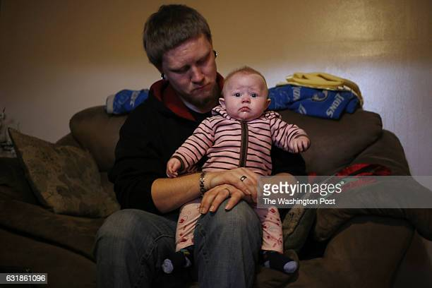 Jeremy Smith holds his daughter four monthold Cynthia Smith in the living room of the one bedroom apartment they share with his wife mother and...