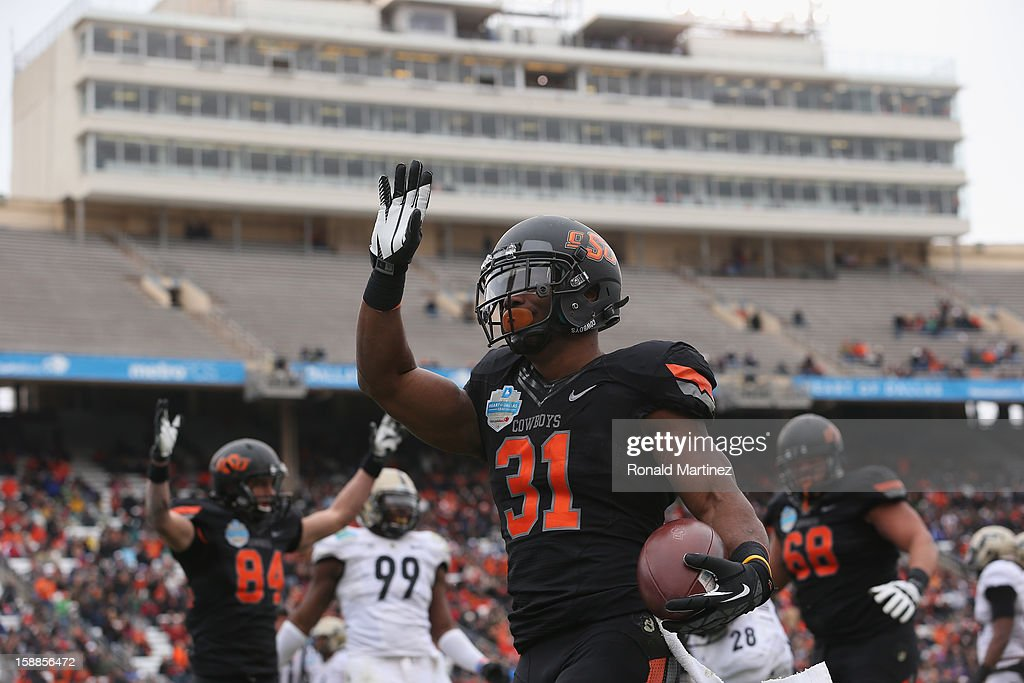 Jeremy Smith #31 of the Oklahoma State Cowboys celebrates a touchdown against the Purdue Boilermakers during the Heart of Dallas Bowl at Cotton Bowl on January 1, 2013 in Dallas, Texas.