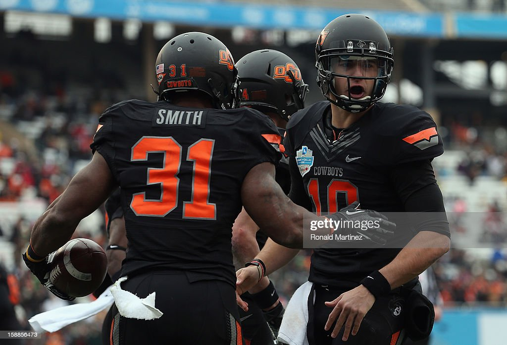 Jeremy Smith #31 of the Oklahoma State Cowboys celebrates a touchdown with Clint Chelf #10 against the Purdue Boilermakers during the Heart of Dallas Bowl at Cotton Bowl on January 1, 2013 in Dallas, Texas.