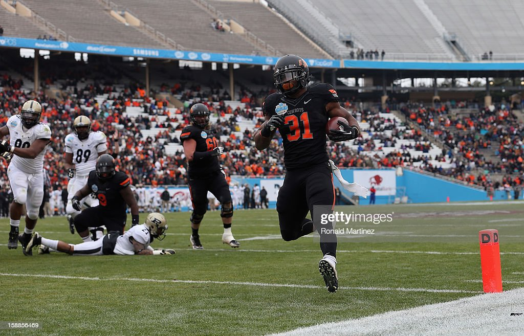 Jeremy Smith #31 of the Oklahoma State Cowboys runs for a touchdown against the Purdue Boilermakers during the Heart of Dallas Bowl at Cotton Bowl on January 1, 2013 in Dallas, Texas.