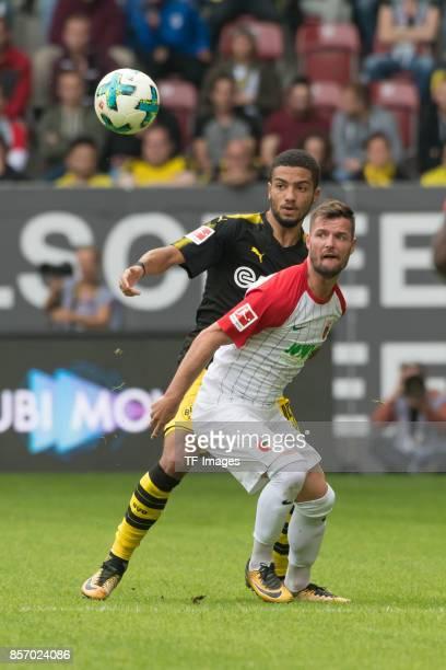 Jeremy Toljan of Dortmund and Marcel Heller of Augsburg battle for the ball during the Bundesliga match between FC Augsburg and Borussia Dortmund at...