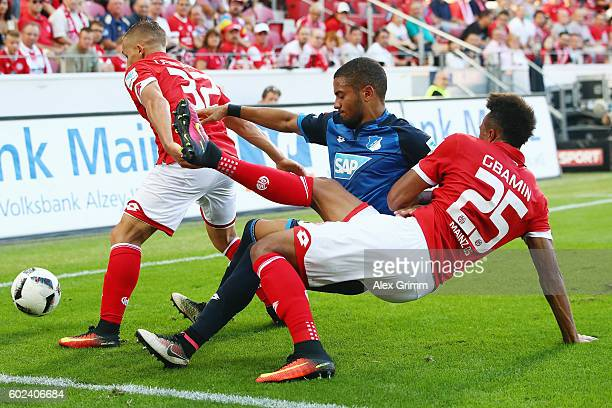 Jeremy Toljan of Hoffenheim is challenged by Pablo de Blasis and JeanPhilippe Gbamin of Mainz during the Bundesliga match between 1 FSV Mainz 05 and...