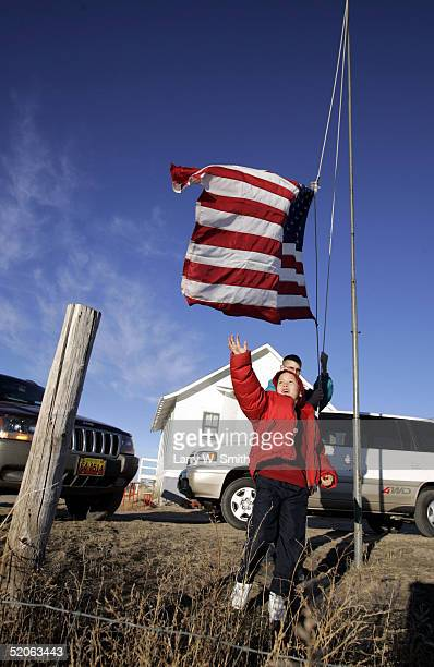 Jeremy Torres a third grade student reaches up towards the US flag as Cody Taylor an eighth grade student raises it before the start of school...