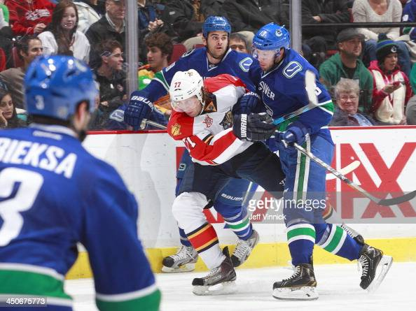 Jeremy Welsh and Tom Sestito of the Vancouver Canucks combine to check Matt Gilroy of the Florida Panthers during their NHL game at Rogers Arena on...