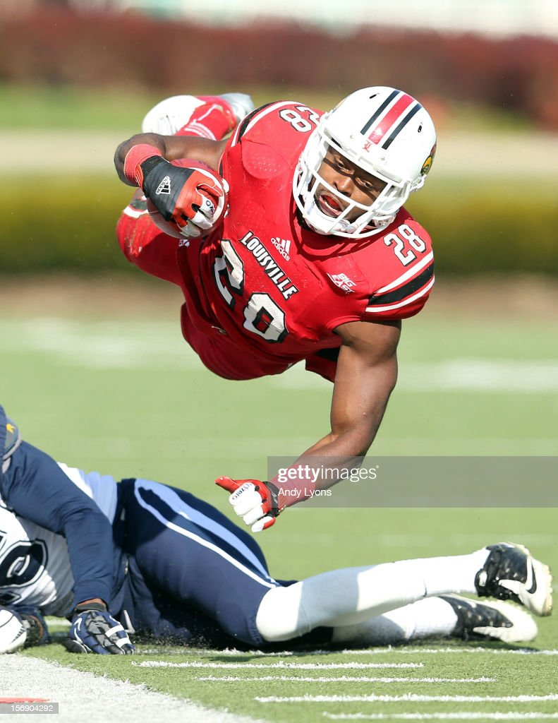 Jeremy Wright #28 of the Louisville Cardinals is tripped up by Bryon Jones #16 of the Connecticut Huskies at Papa John's Cardinal Stadium on November 24, 2012 in Louisville, Kentucky.