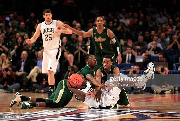 Jerian Grant of the Notre Dame Fighting Irish looks to pass while Hugh Robertson and Anthony Collins of the South Florida Bulls go for the ball...