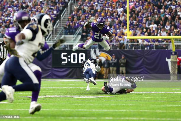 Jerick McKinnon of the Minnesota Vikings leaps with the ball over defender Nickell RobeyColeman of the Los Angeles Rams in the first quarter of the...