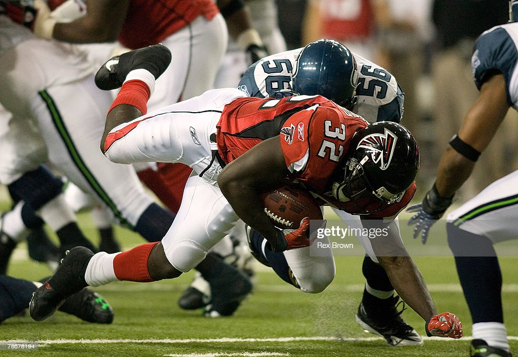 Jerious Norwood #32 of the Atlanta Falcons dives for a first down as he is brought down by LeRoy Hill #56 of the Seattle Seahawks during the second half at Georgia Dome on December 30, 2007 in Atlanta, Georgia. Atlanta defeated Seattle 44-41.