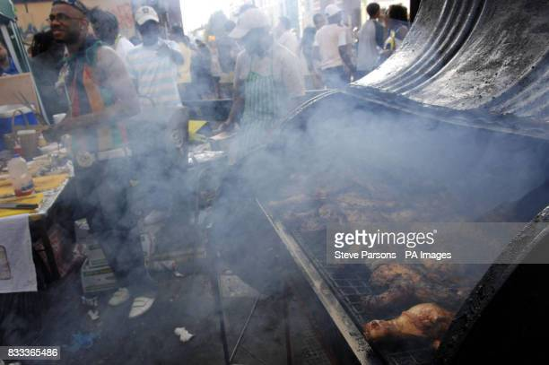 Jerk Chicken is cooked as party goers enjoy the sunshine at the Notting Hill Carnival in West London
