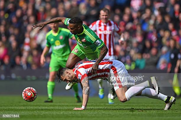 Jermain Defoe of Sunderland and Geoff Cameron of Stoke City compete for the ball during the Barclays Premier League match between Stoke City and...