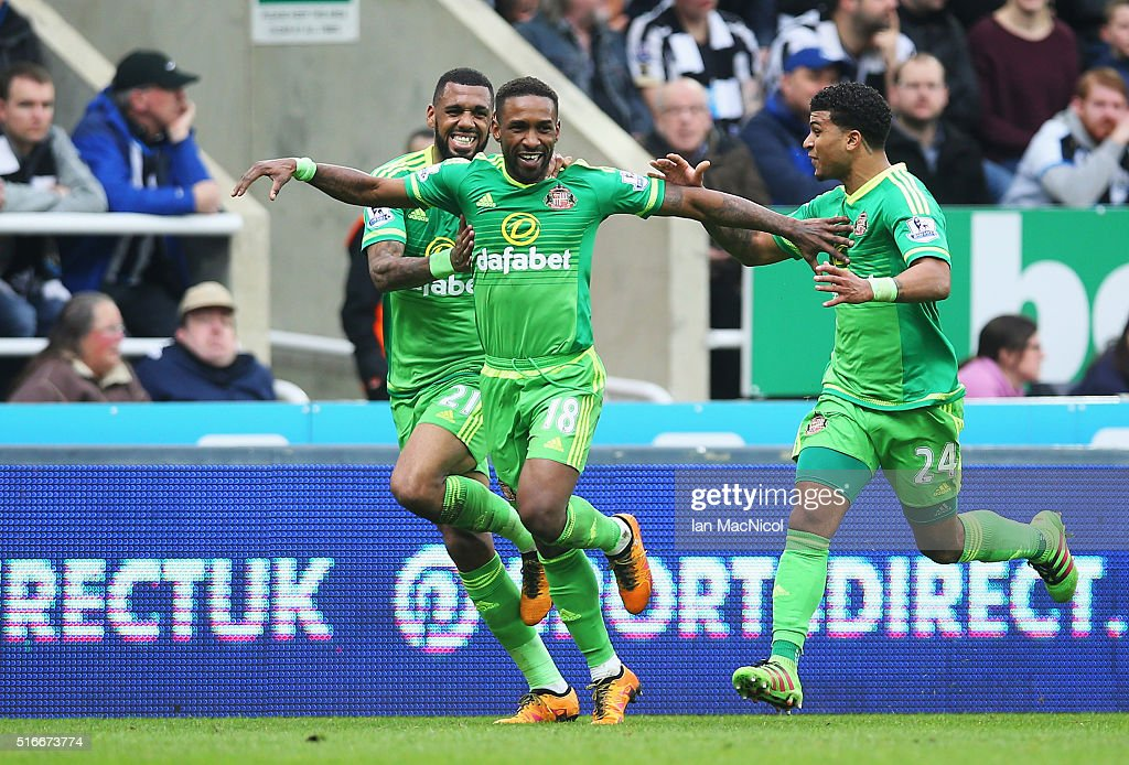 Jermain Defoe of Sunderland (18) celebrates with Yann M'Vila (L) and DeAndre Yedlin (R) as he scores their first goal during the Barclays Premier League match between Newcastle United and Sunderland at St James' Park on March 20, 2016 in Newcastle upon Tyne, United Kingdom.