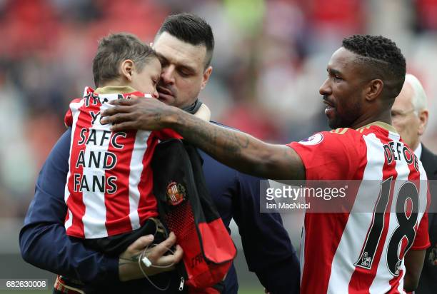 Jermain Defoe of Sunderland hands Bradley Lowery back to his Dad Carl Lowery prior to the Premier League match between Sunderland and Swansea City at...