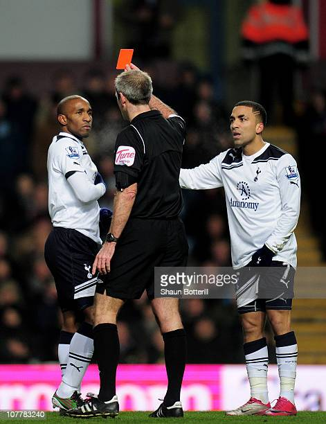 Jermain Defoe of Tottenham is shown the red card as teammate Aaron Lennon protests to the referee during the Barclays Premier League match between...