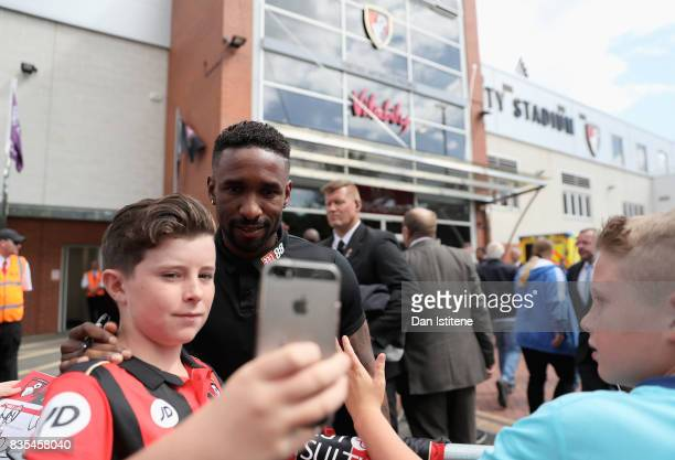 Jermain Dfoe of AFC B ournemouth takes a selfie photograph with a fan outside the stadium prior to the Premier League match between AFC Bournemouth...
