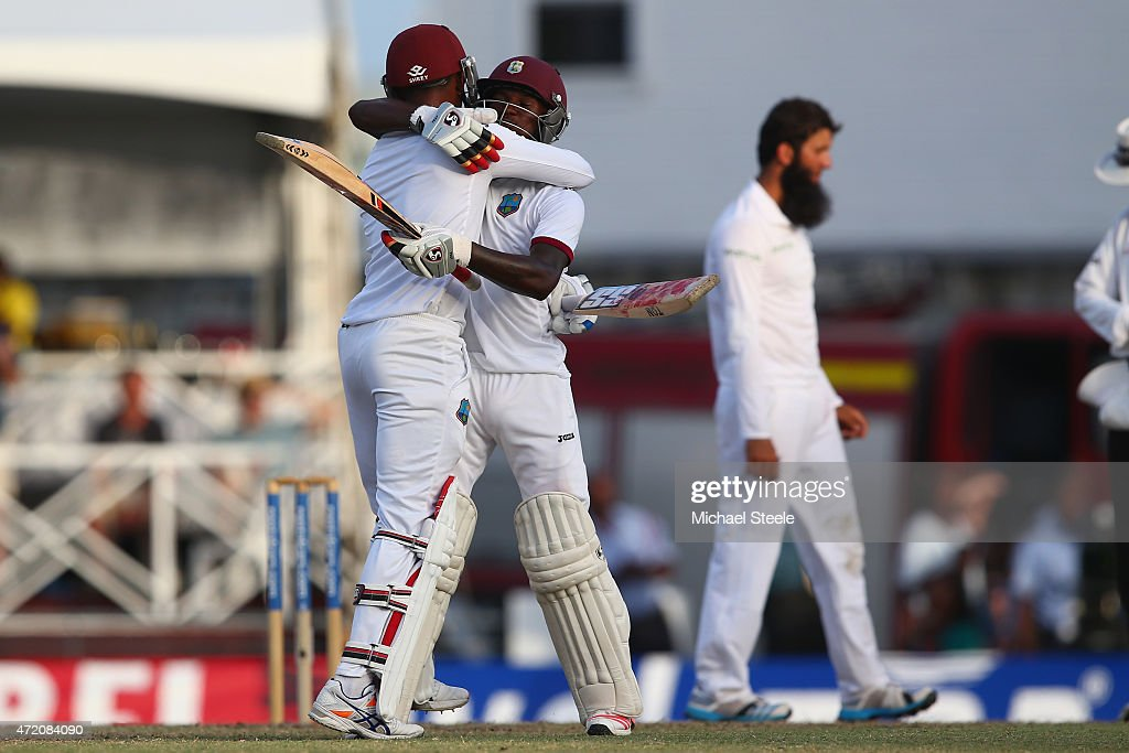 Jermaine Blackwood (R) and Denesh Ramdin (L) of West Indies celebratevictory in the match and drawing the series 1-1 as Moeen Ali (R) of England cuts a lonely figure aduring day three of the 3rd Test match between West Indies and England at Kensington Oval on May 3, 2015 in Bridgetown, Barbados.