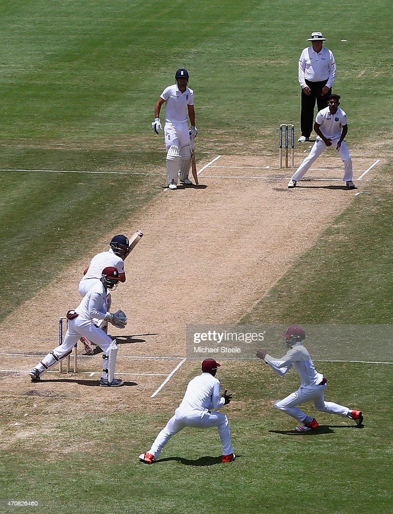 Jermaine Blackwood (R) of West Indies takes a catch off the bowling of Devendra Bishoo to dismiss Jonathan Trott of England during day three of the 2nd Test match between West Indies and England at the National Cricket Stadium in St George's on April 23, 2015 in Grenada, Grenada.