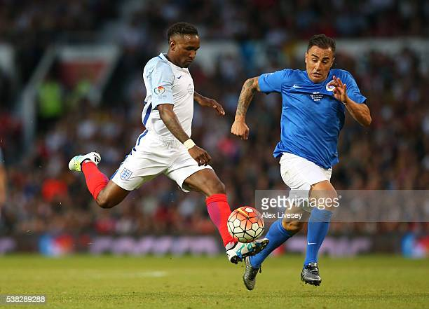 Jermaine Defoe of England beats Fabio Cannavaro of Rest of the World to score their second goal during the Soccer Aid 2016 match in aid of UNICEF at...