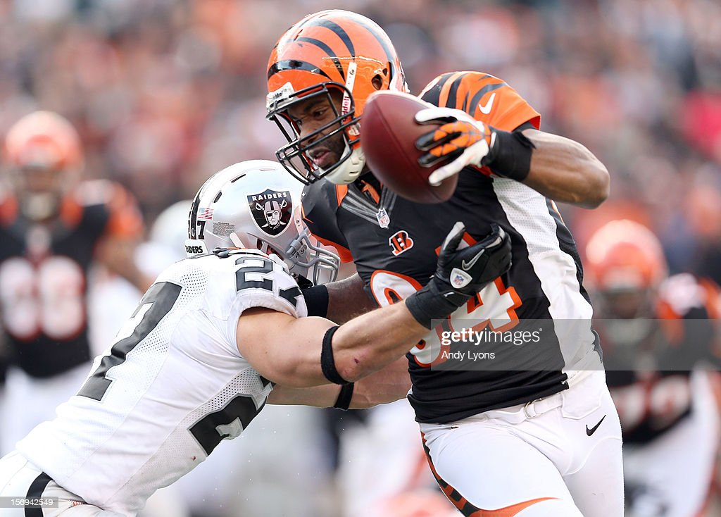 Jermaine Gresham #84 of the Cincinnati Bengals runs for a touchdown while defended by Matt Giordano #27 of the Oakland Raiders during the NFL game at Paul Brown Stadium on November 25, 2012 in Cincinnati, Ohio.