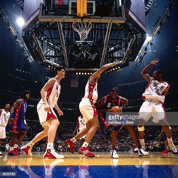 Jermaine O'Neal of the Eastern Conference AllStars looks to shoot against Kobe Bryant and Tim Duncan of the Western Conference AllStars during the...