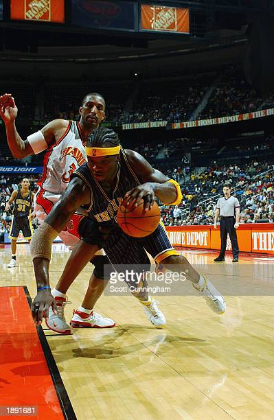 Jermaine O'Neal of the Indiana Pacers looses his balance as he drives against Shareef AbdurRahim of the Atlanta Hawks during the NBA game at Philips...