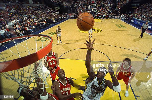 Jermaine O'Neal of the Indiana Pacers shoots over Glenn Robinson and Shareef AbdurRahim of the Atlanta Hawks during the NBA game at Conseco...