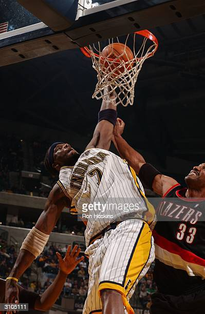 Jermaine O'Neal of the Indiana Pacers shoots over Shareef AbdurRahim of the Portland Trailblazers in NBA action March 17 2004 at Conseco Fieldhouse...
