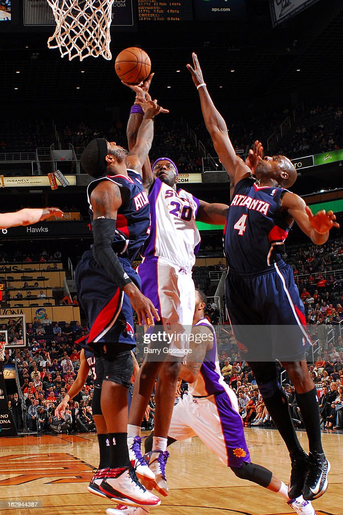 Jermaine O'Neal #20 of the Phoenix Suns puts a shot up between Josh Smith #5 and Anthony Tolliver #4 of the Atlanta Hawks on March 1, 2013 at U.S. Airways Center in Phoenix, Arizona.