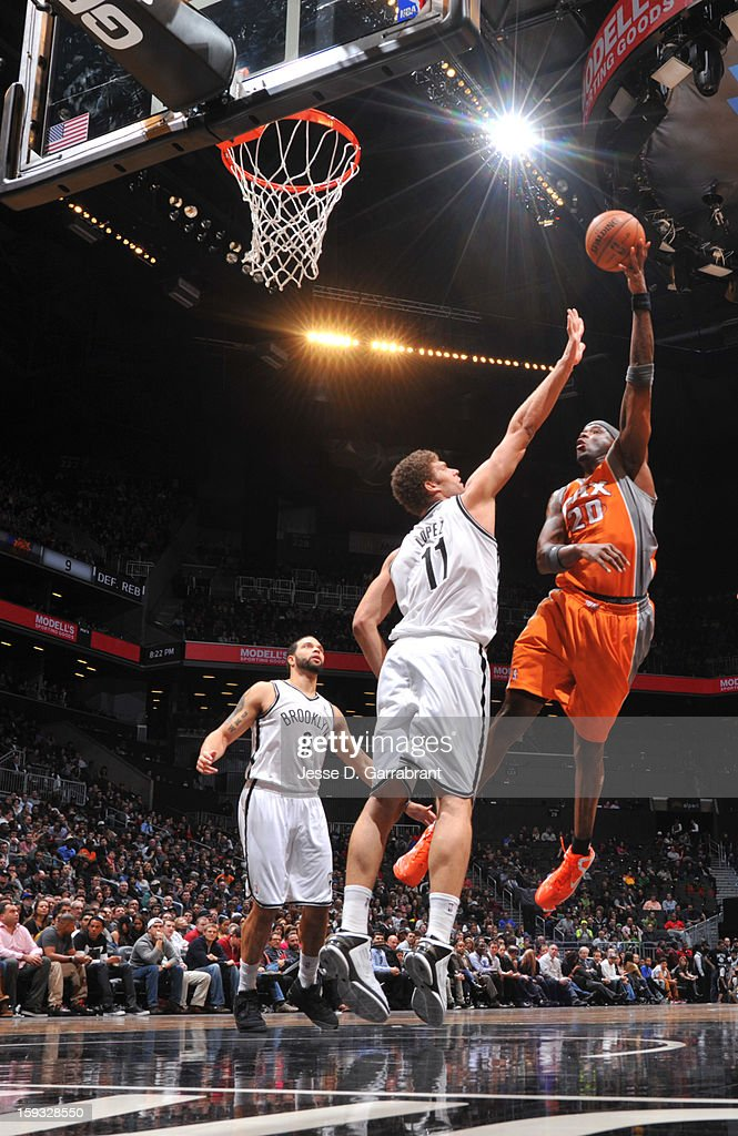 Jermaine O'Neal #20 of the Phoenix Suns taking a shot against Brook Lopez #11 of the Brooklyn Nets during the game at the Barclays Center on January 11, 2013 in Brooklyn, New York.