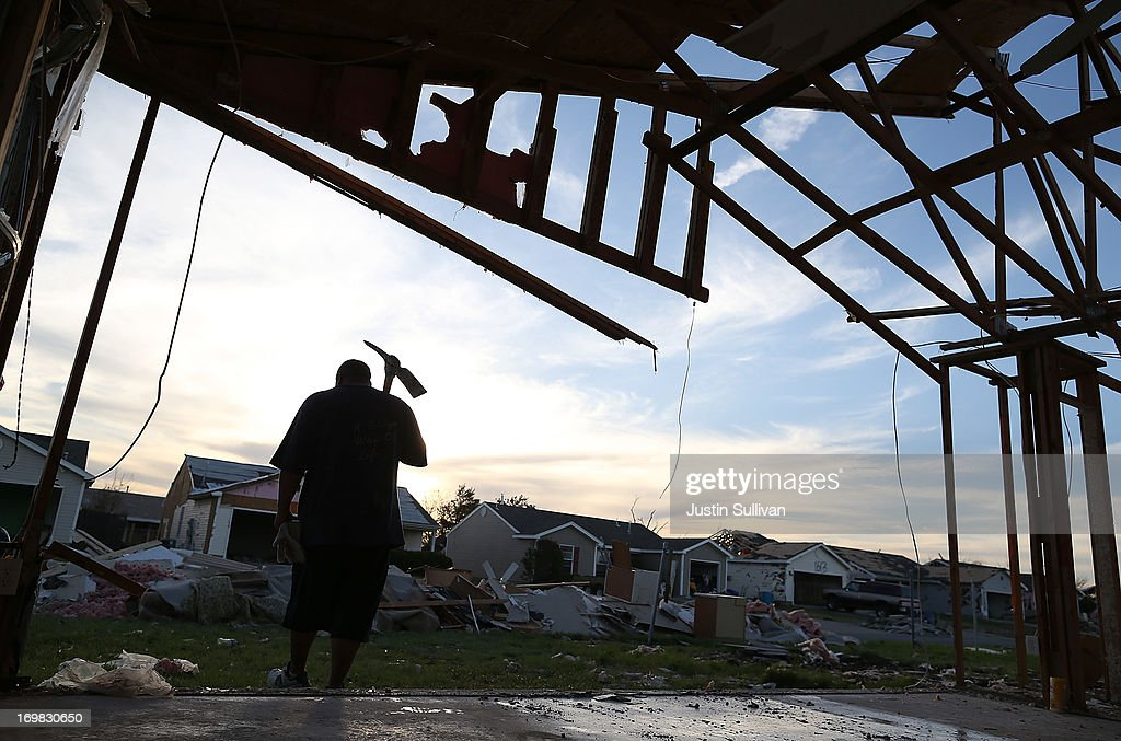 Jermaine Scallion holds a pick axe while he works on a home damaged by a tornado on June 2, 2013 in Moore, Oklahoma. Residents of Moore, Oklahoma continue to recover and sift through the remains of their homes two weeks after a devastating EF-5 tornado ripped through the town killing 24 people and destroying hundreds of homes and businesses.
