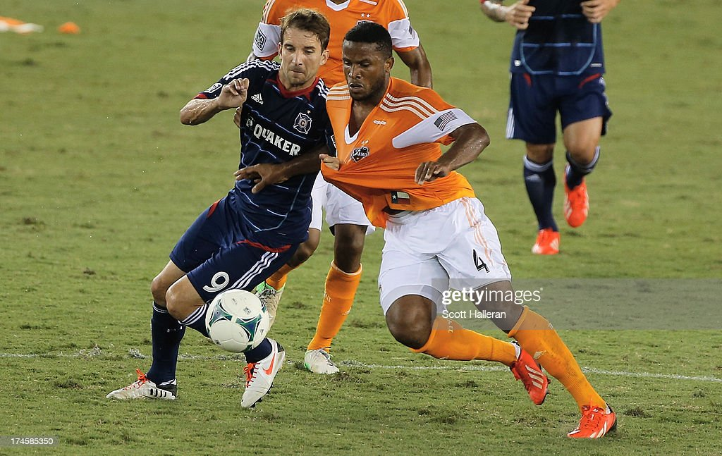 Jermaine Taylor #4 of the Houston Dynamo battles for the ball against Mike Magee #9 of the Chicago Fire at BBVA Compass Stadium on July 27, 2013 in Houston, Texas.
