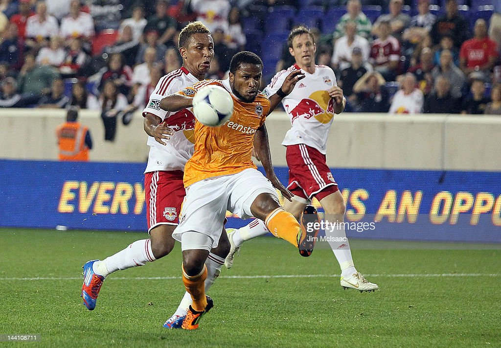 <a gi-track='captionPersonalityLinkClicked' href=/galleries/search?phrase=Jermaine+Taylor+-+Soccer+Player&family=editorial&specificpeople=13524207 ng-click='$event.stopPropagation()'>Jermaine Taylor</a> #4 of the Houston Dynamo clears the ball on a scoring chance against <a gi-track='captionPersonalityLinkClicked' href=/galleries/search?phrase=Juan+Agudelo&family=editorial&specificpeople=6850559 ng-click='$event.stopPropagation()'>Juan Agudelo</a> #17 of the New York Red Bulls at Red Bull Arena on May 9, 2012 in Harrison, New Jersey.
