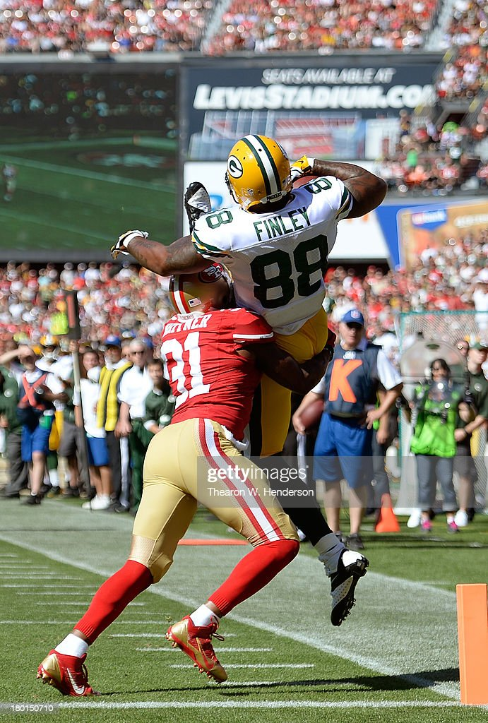 Jermichael Finley #88 of the Green Bay Packers makes the catch but is taken out of bounds in the air by Donte Whitner #31 of the San Francisco 49ers for an incomplete pass during the third quarter at Candlestick Park on September 8, 2013 in San Francisco, California.