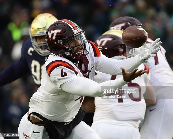 Jerod Evans of the Virginia Tech Hokies reaches for the ball after it was snapped over his head against the Notre Dame Fighting Irish at Notre Dame...
