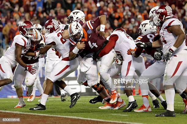 Jerod Evans of the Virginia Tech Hokies runs for a touchdown against the Arkansas Razorbacks during the Belk Bowl at Bank of America Stadium on...