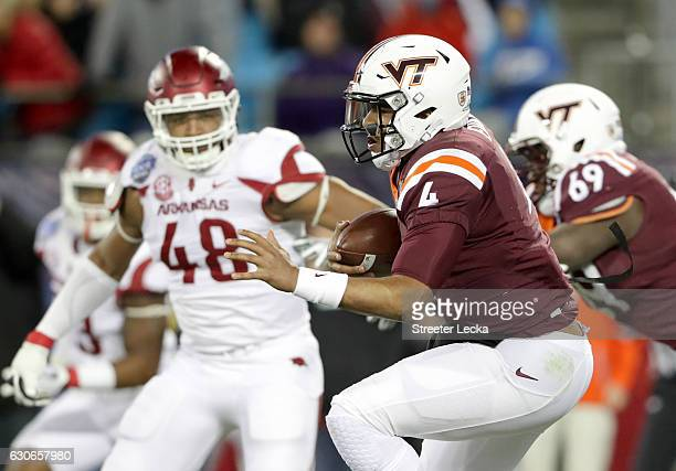 Jerod Evans of the Virginia Tech Hokies runs with the ball against Deatrich Wise Jr #48 of the Arkansas Razorbacks during the Belk Bowl at Bank of...