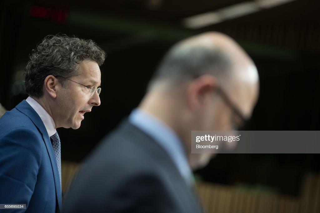 Jeroen Dijsselbloem, Dutch finance minister and head of the group of euro-area finance ministers, left, speaks during a news conference following a Eurogroup meeting of finance ministers in Brussels, Belgium, on Monday, March 20, 2017. Wolfgang Schaeuble, Germany's finance minister, said to reporters ahead of the meeting of euro-area finance ministers We'll get a report on Greece, but the mission isn't completed. Photographer: Jasper Juinen/Bloomberg via Getty Images