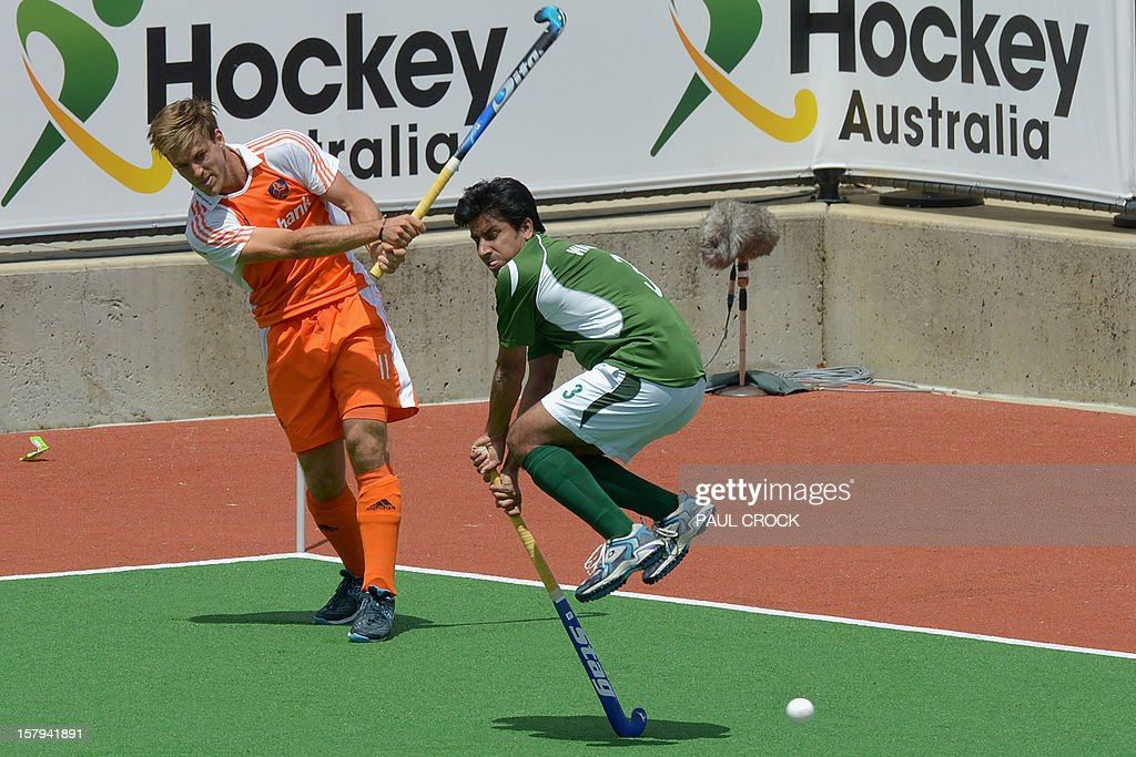 Jeroen Hertzberger of The Netherlands (L) passes the ball as Waseem Ahmed of Pakistan (R) leaps during their semi final match at the men's Hockey Champions Trophy in Melbourne on December 8, 2012. IMAGE STRICTLY RESTRICTED TO EDITORIAL USE - STRICTLY NO COMMERCIAL USE AFP PHOTO / Paul CROCK