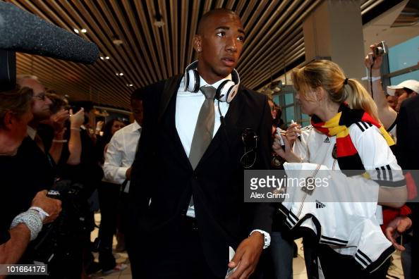 Jerome Boateng is surrounded by fellow passengers on his way to boarding during a fan event before the departure of the German national football team...