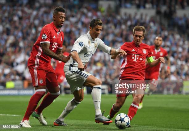 Jerome Boateng of Bayern Muenchen and Philipp Lahm of Bayern Muenchen attempt to tackle Cristiano Ronaldo of Real Madrid during the UEFA Champions...