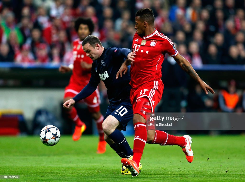 Jerome Boateng (R) of Bayern Muenchen challenges Wayne Rooney (C) of Manchester United during the UEFA Champions League Quarter Final second leg match between FC Bayern Muenchen and Manchester United at Allianz Arena on April 9, 2014 in Munich, Germany.