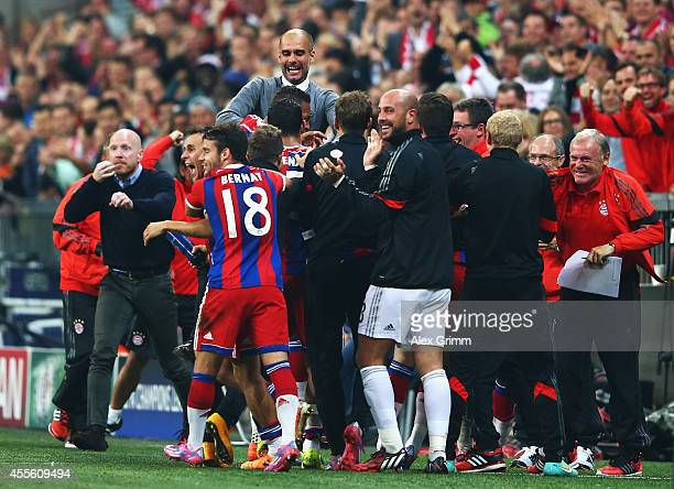 Jerome Boateng of Bayern Muenchen is mobbed by team mates including coach Josep Guardiola of Bayern Muenchen after his goal during the UEFA Champions...