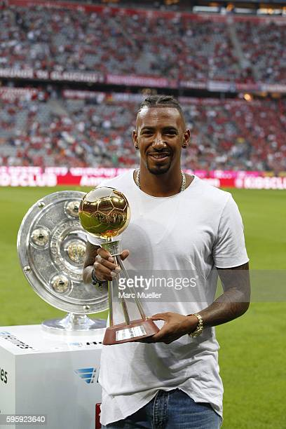Jerome Boateng of Bayern Munich poses with his 'soccer player of the year in Germany' Cup before the Bundesliga match between Bayern Muenchen and...