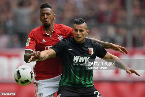 Jerome Boateng of FC Bayern Muenchen and Raul Bobadilla of Augsburg compete for the ball during the Bundesliga match between Bayern Muenchen and FC...