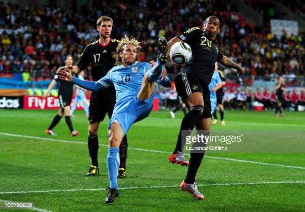 Jerome Boateng of Germany challenges Diego Forlan of Uruguay during the 2010 FIFA World Cup South Africa Third Place Playoff match between Uruguay...