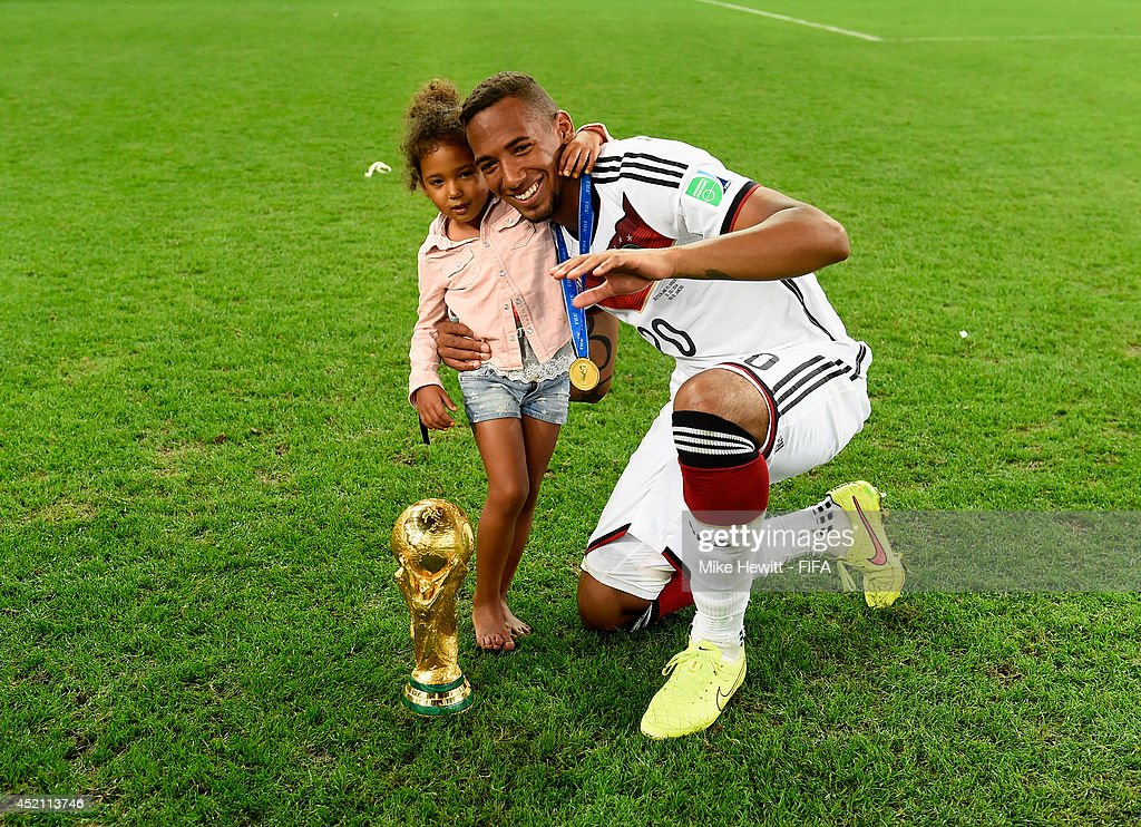 Jerome Boateng of Germany poses for photographs with his daughter and the World Cup trophy after the 2014 FIFA World Cup Brazil Final match between Germany and Argentina at Maracana on July 13, 2014 in Rio de Janeiro, Brazil.