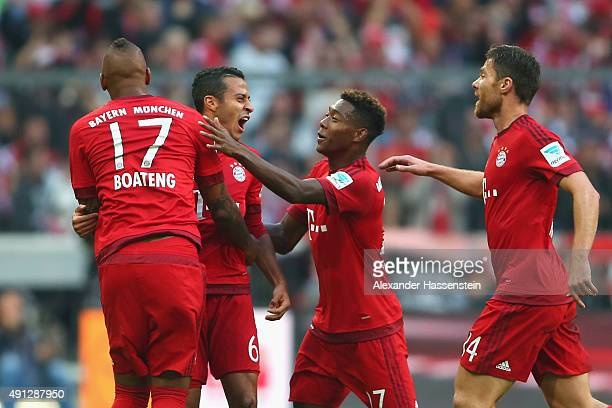 Jerome Boateng of Muenchen celebrates the firts team goal witrh his team mates Thiago David Alaba and Xabi Alonso during the Bundesliga match between...